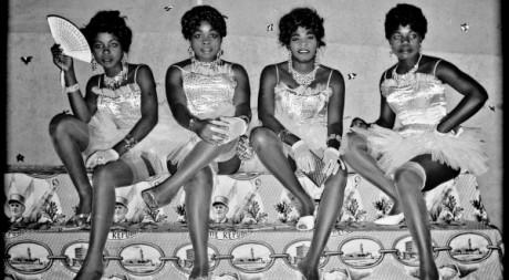 Jean Depara - Quatre danseuses assises sur un plaid à l'effigie du général De Gaulle- COURTESY Galerie Maison Revue Noire